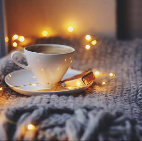 cozy winter or autumn morning at home hot coffee with gold metallic spoon, warm blanket, garland and candle lights, swedish hygge concept
