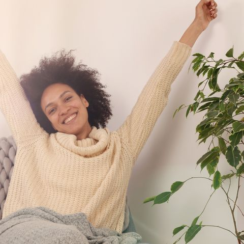 Cozy Woman waking up , stretching , relaxing at home. Carefree people, happiness, lifestyle concept