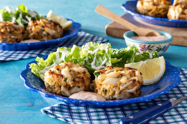crab cakes two on blue plate with side salad