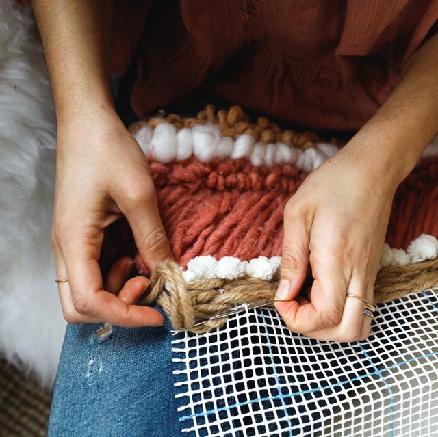 woman making tapestry with yarn