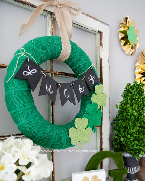 """green burlap wreath with three glitter foam shamrocks and a """"lucky"""" banner tied across it it is hanging on a window frame which is sitting on a mantel"""