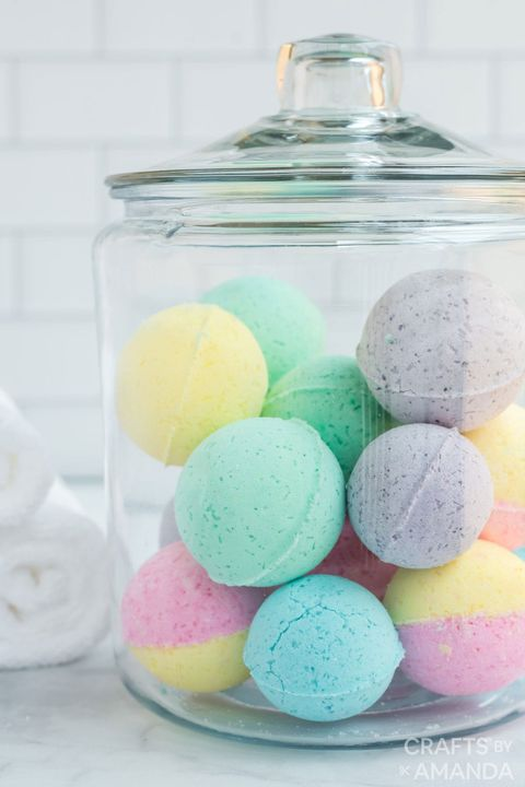 bath bombs, shaped like balls and in pastels colors including lavender, green and yellow, in glass canister
