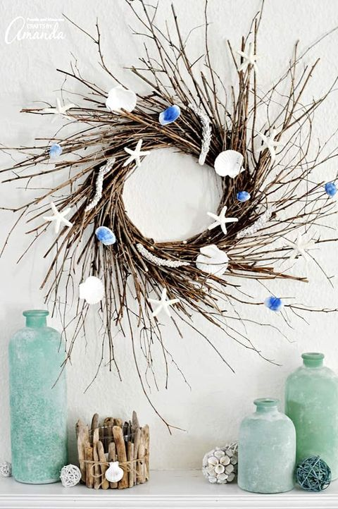 wreath made of sticks tied together in a circle with mini shells and starfish on it
