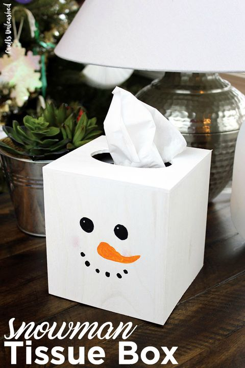 white tissue box with a snowman face painted on it, including a long orange nose, round black eyes and black dots for a smiling mouth it's sitting on an end table in front of a lamp and plant