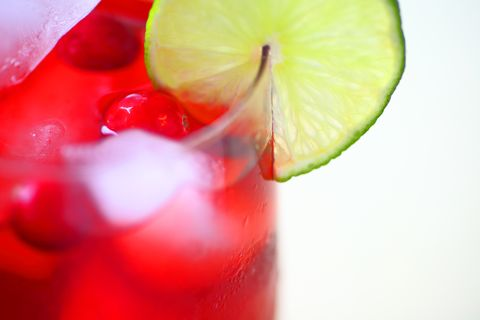 High Angle Close-Up Of Cranberry Juice With Lime Over White Background