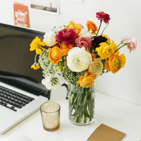 calm tidy desk with flowers and glass and laptop