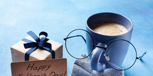 Creative breakfast on Happy Fathers Day with gift box, funny face from cup of coffee, eyeglasses and bowtie.