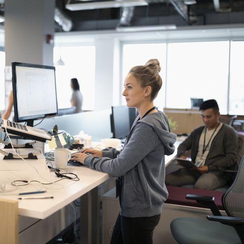 سيدة أعمال مبدعة تقف على المكتب ، تستخدم الكمبيوتر المحمول والكمبيوتر في مكتب بمخطط مفتوح