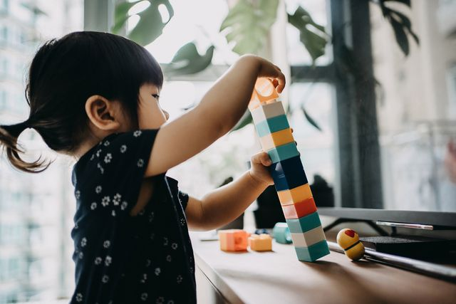 creative little toddler girl playing with colourful building blocks at home