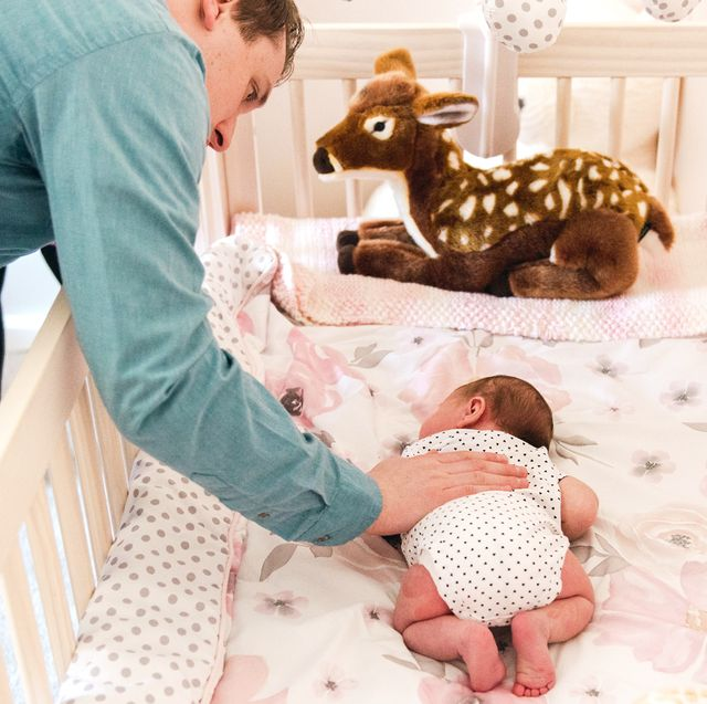 dad soothing baby in crib