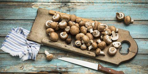 crimini mushrooms on wooden chopping board