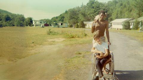 man die een andere man duwt in een rolstoel voor een grasveld, bomen en huizen