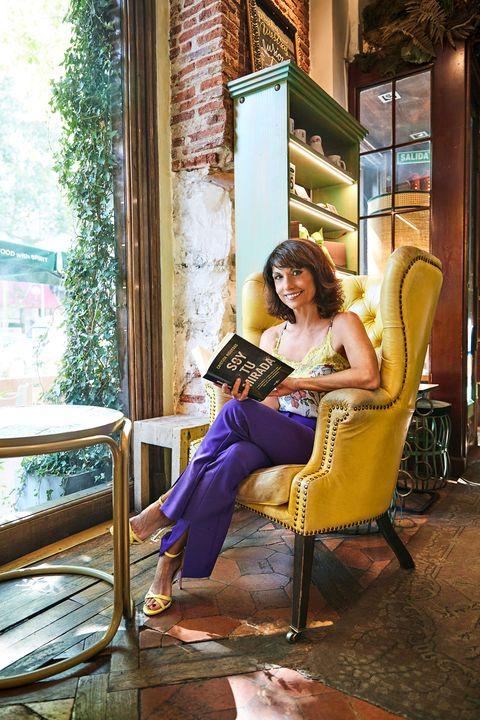 la actriz y escritora mira a cámara sentada en su sillón con su nuevo libro entre las manos