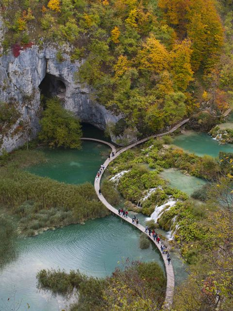 tourists walk on the main boardwalk in the centre of plitvice lakes national park during autumn the park was the first natural site to be included on unesco's world heritage list