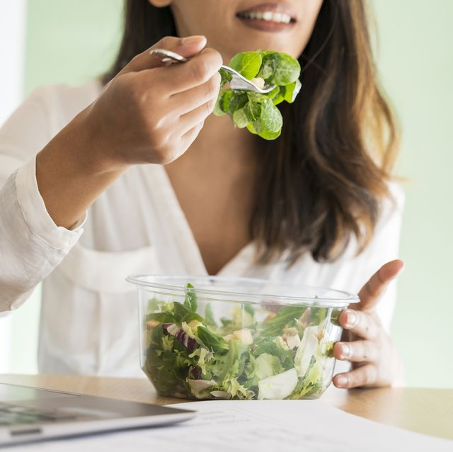 crop view of young architect eating mixed salad at desk