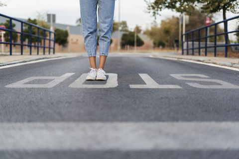 crop view of young woman standing on the word 'stop' on the street