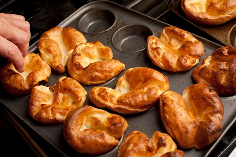 Cropped Hand By Yorkshire Puddings On Baking Sheets At Home
