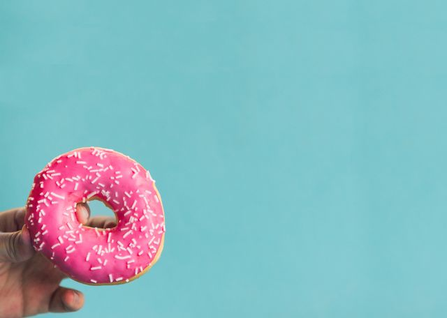 cropped hand holding donut against blue background