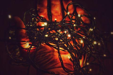 Hand Holding Illuminated Christmas Lights In Darkroom