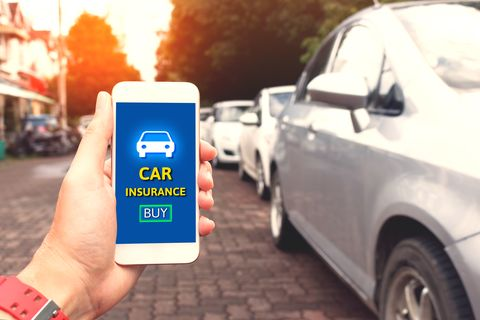 Cropped Hand Holding Mobile Phone With Car Insurance Text At Footpath