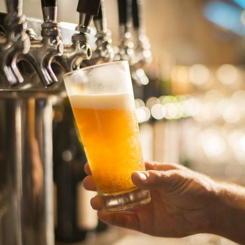 Cropped hand of bartender filling beer from tap at bar