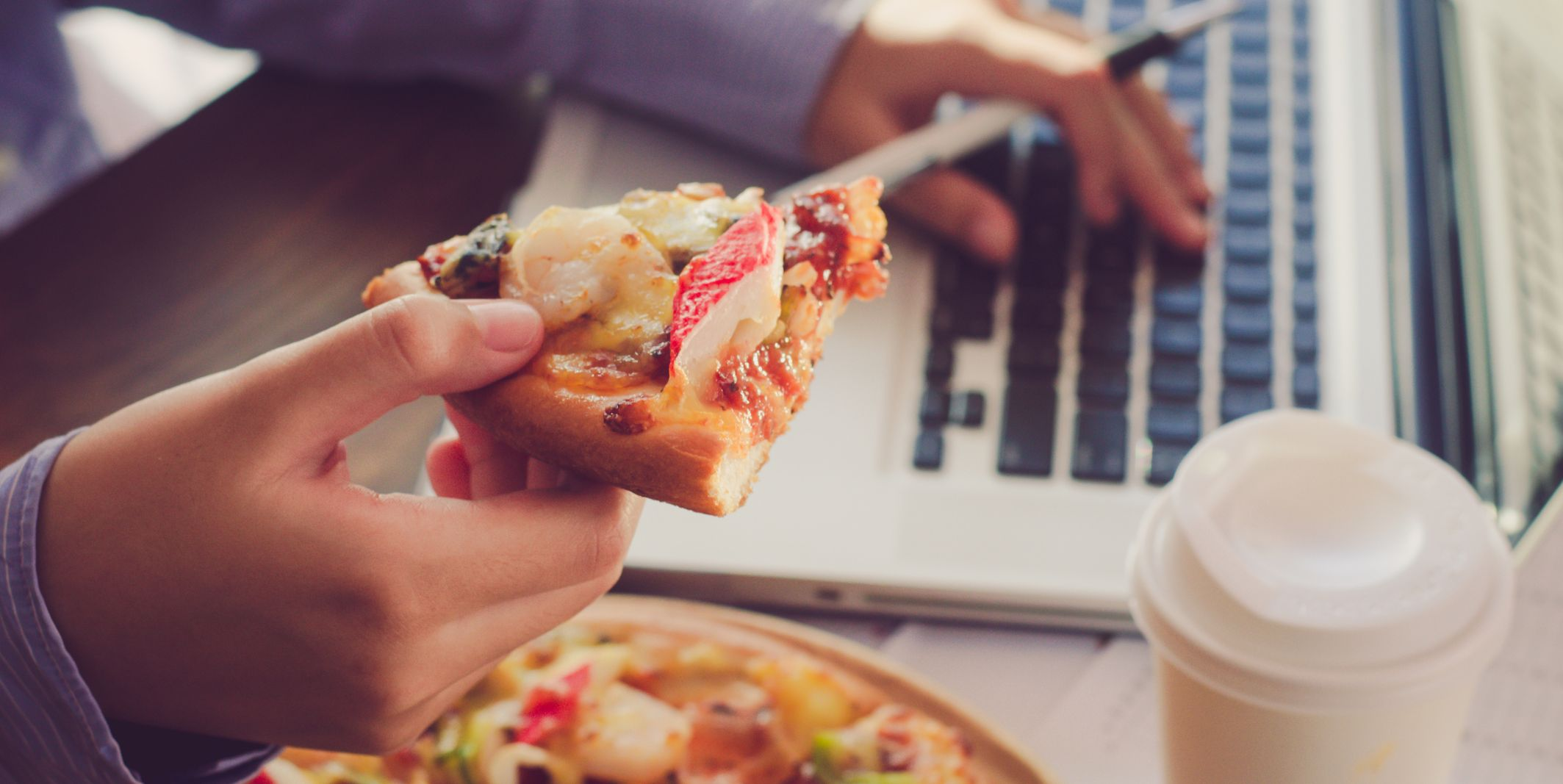 Cropped Hand Of Business Person Holding Pizza Slice In Office