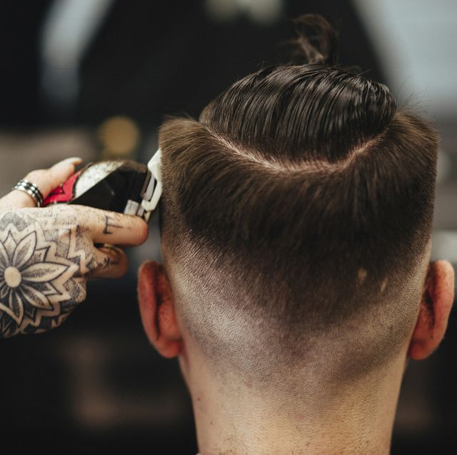 cropped hand of female barber cutting male customer's hair in salon