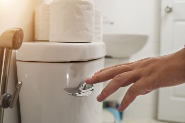 cropped hand of man flushing water