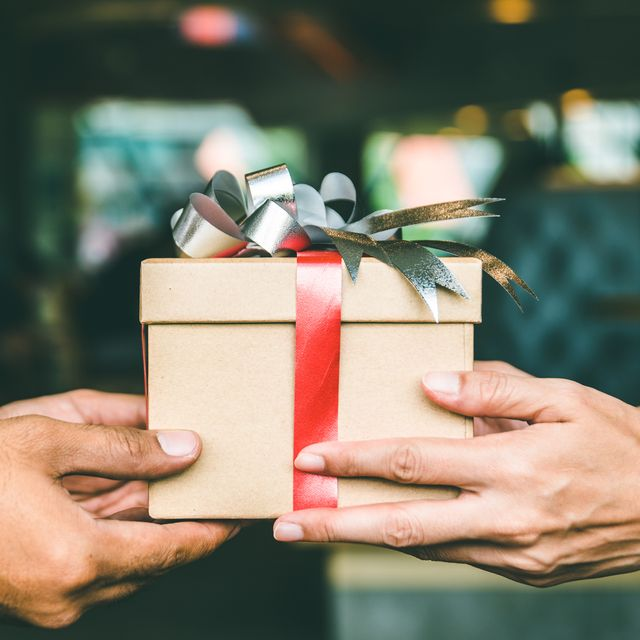 cropped hand of man giving christmas present to female friend