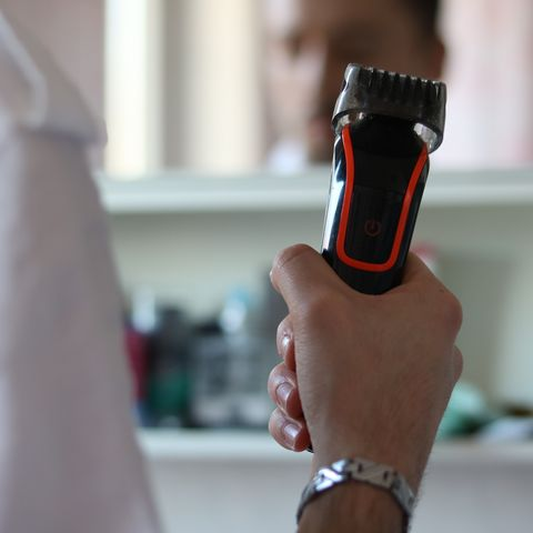 cropped hand of man holding shaver at home