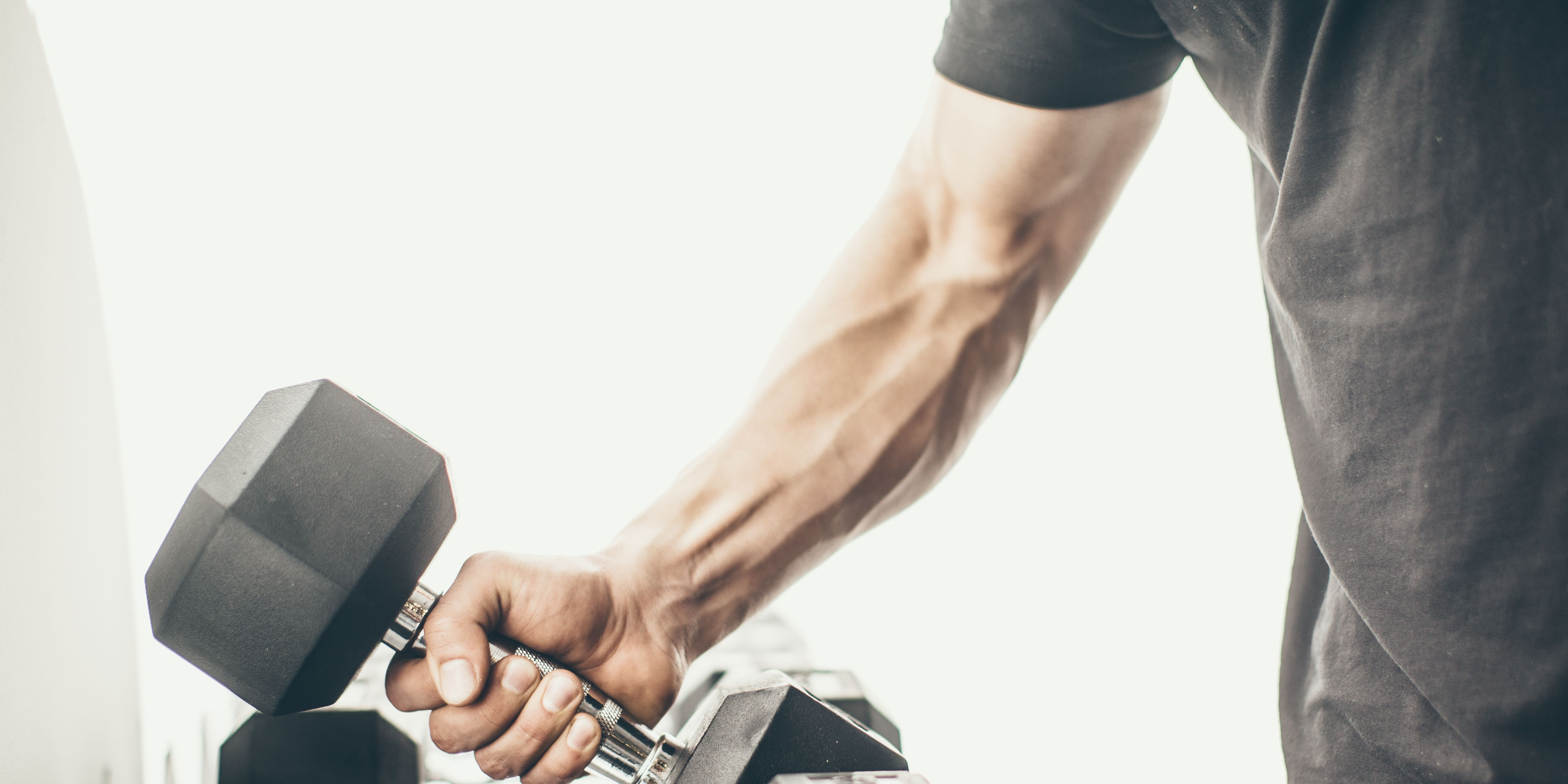 Cropped Hand Of Muscular Man Holding Dumbbell Against White Background