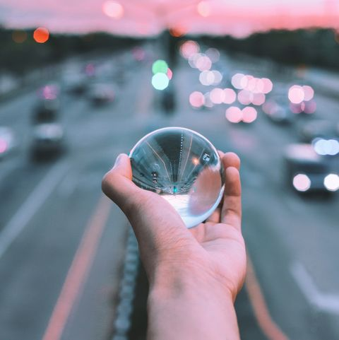 Cropped Hand Of Person Holding Crystal Ball Against Road During Sunset