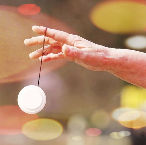 Cropped Hand Of Person Holding Hypnosis Equipment Against Illuminated Lights