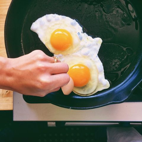 cropped hand of woman cooking omelet in pan on stove