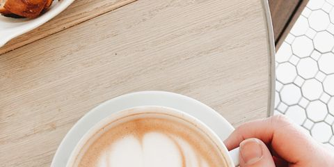 Cropped Hand Of Woman Holding Coffee Cup On Table