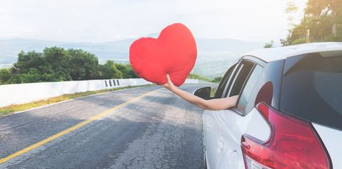 Cropped Hand Of Woman Holding Heart Shape In Car Against Sky