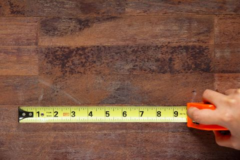 Cropped Hand Of Woman Holding Measuring Tape On Wooden Table