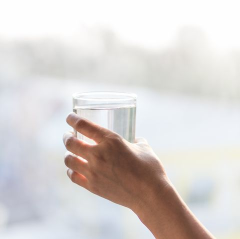 Cropped Hand Of Woman Holding Water In Glass