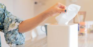 Cropped Hand Of Woman Pulling Tissue From Box On Table