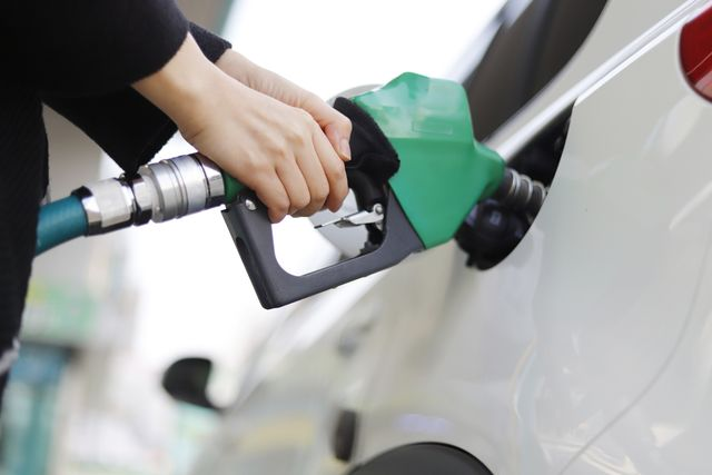cropped hand of woman refueling car