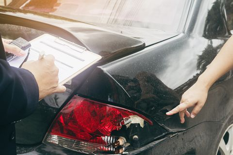 Cropped Hand Of Woman Showing Damaged Car To Agent