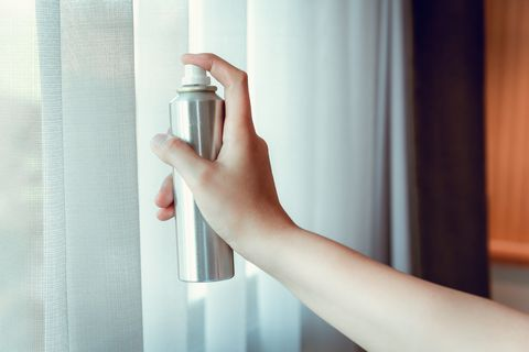Cropped Hand Of Woman Spraying Air Freshener By Window