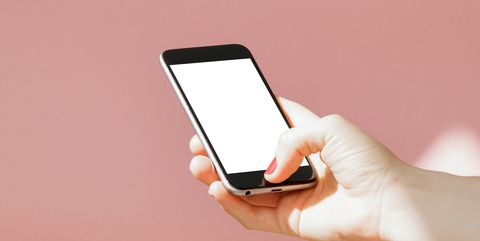 Cropped Hand Of Woman Using Mobile Phone Against Colored Background