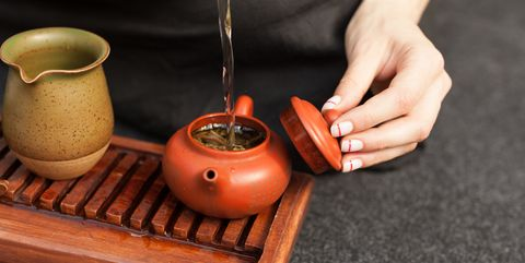 Cropped Hand Pouring Water In Tea