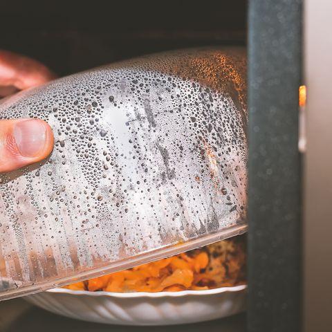 Cropped Hand Preparing Food In Microwave