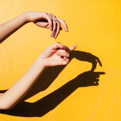 cropped hands gesturing against shadow on yellow background