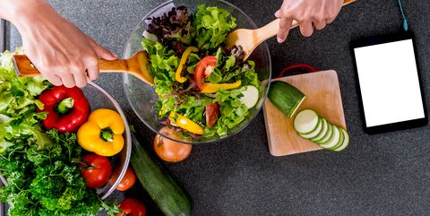 Cropped Hands Making Salad In Bowl