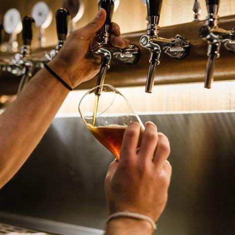 Cropped Hands Of Bartender Filling Beer Glass At Bar