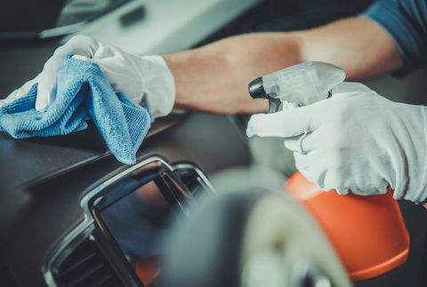 cropped hands of man cleaning dashboard in car