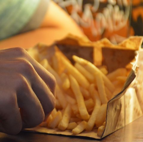 cropped hands of man eating french fries